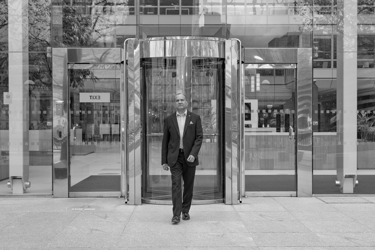 A man walking out of an office building in Black & White.