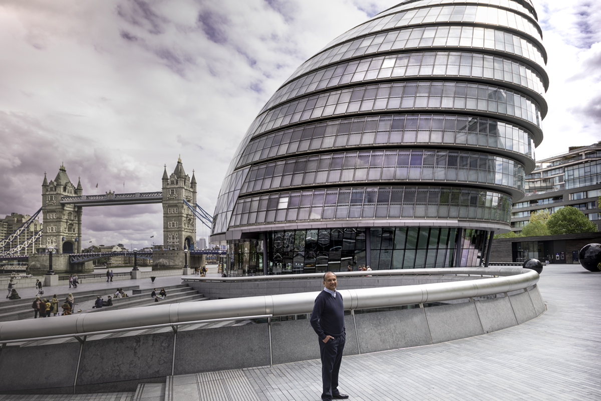 A man standing in front of Tower Bridge and the offices of the London Mayor.